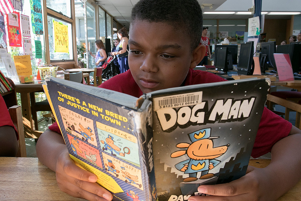 ". The Fitchburg Public Library held a summer Reading Kickoff Party on Thursday, June 27, 2019. Enjoying the book ""Dog Man\"" during the party is Brighton Wells, 9, from Fitchburg. SENTINEL & ENTERPRISE/JOHN LOVE"