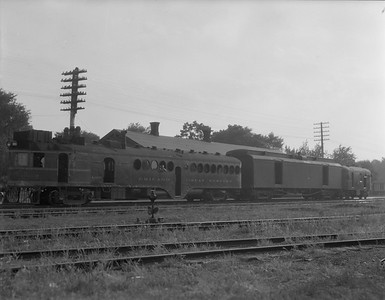 2009.026.07.14233--ritzman 4x5 negative--CGW--McKeen motorcar 1003 with passenger train 4--Sycamore IL--1936 0717. Baggage car #1025.