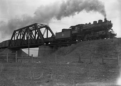 2009.026.01.09460--ritzman 5x7 negative--CMStP&P--steam locomotive 2-6-2 K1as 944 crossing C&NW overpass with freight train action--east of DeKalb IL--1943 0401. Southbound.