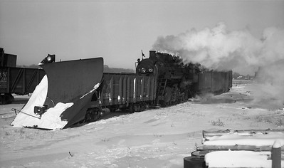 2009.026.01.09474--ritzman PC negative--CMStP&P--steam locomotive 2-6-2 K1as 951 with snowplow extra--DeKalb IL--1947 0104. 12:00 noon. 12 inches snow 1/3/1947 and engine 424 and plow alone went thru as extra 3:00pm on 1/3/1947. Drifted at night hence 951 with plow south 1/4/1947. FRR