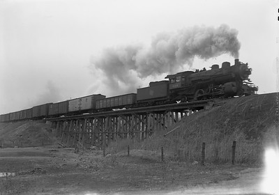 2009.026.01.09461--ritzman 5x7 negative--CMStP&P--steam locomotive 2-6-2 K1as 944 crossing C&NW overpass with freight train action--north of DeKalb IL--1943 0723. Looking north.