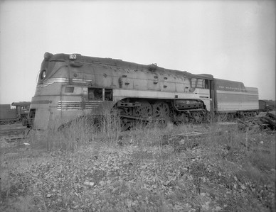 """2009.026.01.8009--ritzman 4x5 negative--CMStP&P--steam locomotive 4-6-4 F-7 102 (dead) after throwing rod--Bensenville IL--1950 1117. """"102 was in Morton Grove Hiawatha mess, threw rod on right side about two months ago."""" FRR"""