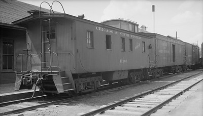 2009.026.12.11314--ritzman 116 neg--C&NW--wooden caboose 11760 on rear of freight train at depot--Cuba City WI--1948 0425