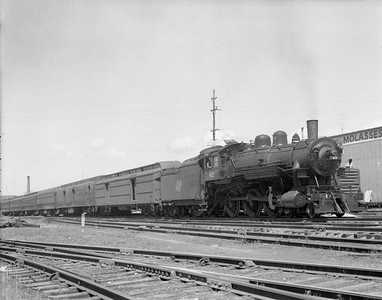 """2009.026.01.10194--ritzman 4x5 negative--C&NW--steam locomotive 4-6-0 R-1 62 on passenger train 26 to fill in for ailing engine--DeKalb IL--1953 0722. On train #26, engine #62 relieved engine #646 at Rochelle due to slipped tire, engine #62 failed at DeKalb due to """"brass trouble."""" Train #26 went on to Chicago with F-M road-switcher #1605 substituted. See FRR notes 7/6/1953."""