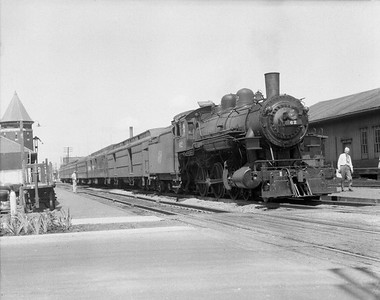 """2009.026.01.10195--ritzman 4x5 negative--C&NW--steam locomotive 4-6-0 R-1 62 on passenger train 26 to fill in for ailing engine--DeKalb IL--1953 0722. On train #26, engine #62 relieved engine #646 at Rochelle due to slipped tire, engine #62 failed at DeKalb due to """"brass trouble."""" Train #26 went on to Chicago with F-M road-switcher #1605 substituted. See FRR notes 7/6/1953."""