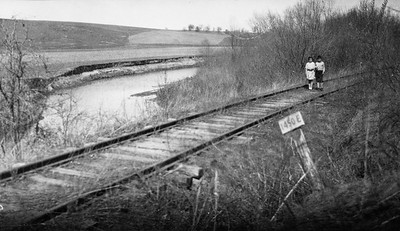 2009.026.2.35.004--ritzman print--C&NW--view of New Diggings spur looking northeast--one mile east of Strawbridge WI--1934 0429. Allyn and Janet Ritzman standing on tracks.