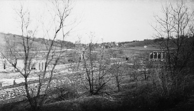 2009.026.2.35.005--ritzman print--C&NW--view of abandoned mine buildings--New Diggings WI--1934 0429. Ritzman's car visible to left of building at right.