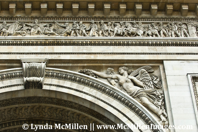 Intricate stone carvings on Arc de Triomphe.