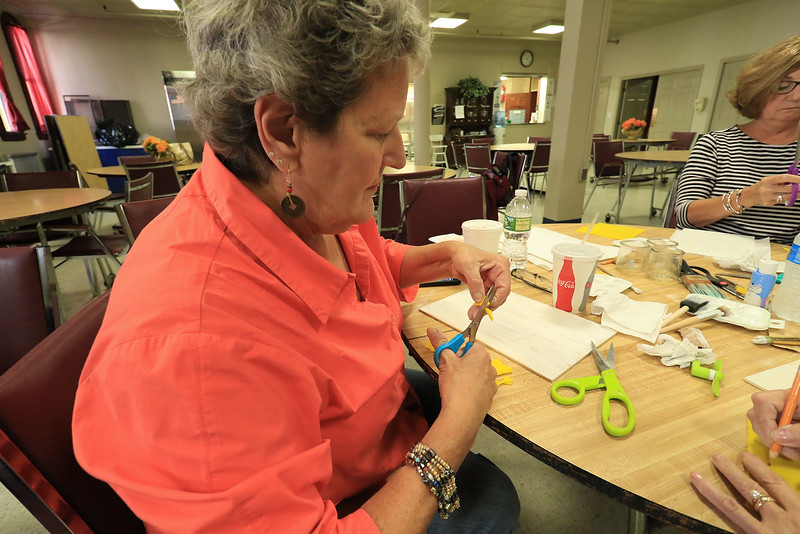 Members of the Fitchburg Senior Center made Mum Welcome Signs out of wood, paint and felt on Thursday at the center. Kathleen Dionne cuts some flower petals for the flowers to be put on the piece. SENTINEL & ENTERPRISE/JOHN LOVE