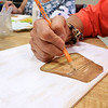 Members of the Fitchburg Senior Center made Mum Welcome Signs out of wood, paint and felt on Thursday at the center. Kathleen Dionne draws and paints a pot on the piece of wood to help create a spot for the flowers to be put on the piece. SENTINEL & ENTERPRISE/JOHN LOVE