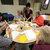 Members of the Fitchburg Senior Center made Mum Welcome Signs out of wood, paint and felt on Thursday at the center. Instructor Beverly McCarthy shows member how to create flower petals. SENTINEL & ENTERPRISE/JOHN LOVE