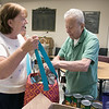 The Fitchburg Senior Center has a  meat, bread and pastry outreach program twice a week. Seniors or veterans can come in and get some food assistance if they need it. Christine grenier gets some help with some canned food by volunteer Paul Thonis during the program on Friday, August 2, 2019. SENTINEL & ENTERPRISE/JOHN LOVE