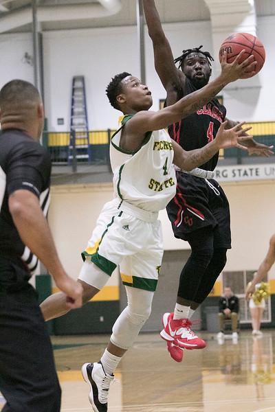 Fitchburg State University basketball played Clark University on Wednesday night, Nov. 13, 2019. FSU's #4 Devon Johnson tries to a shot by CU's #4 Biko Gayman. SENTINEL & ENTERPRISE/JOHN LOVE