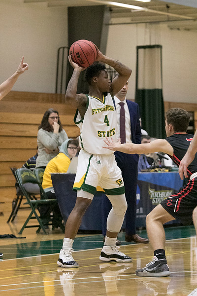 Fitchburg State University basketball played Clark University on Wednesday night, Nov. 13, 2019. FSU's #4 Devon Johnson looks for a teammate to pass to. SENTINEL & ENTERPRISE/JOHN LOVE