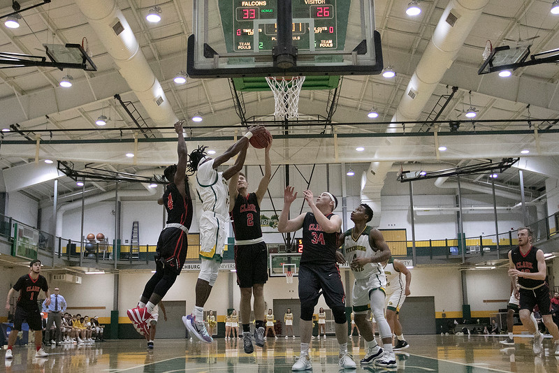 Fitchburg State University basketball played Clark University on Wednesday night, Nov. 13, 2019. FSU's #24 Nicholas Tracy fights for a rebound with CU's #4 Biko Gayman and #2 Joel Arteaga during action in the game. looking on under the basket is CU's #34 Matthew Waggett and FSU's #4 Devon Johnson. SENTINEL & ENTERPRISE/JOHN LOVE