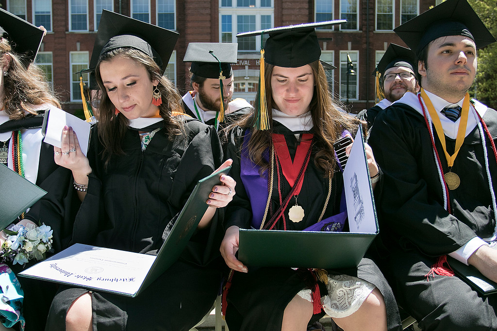. The 123rd Commencement ceremony for Undergraduates was held at Fitchburg State University on Saturday, May 18, 2019. Graduates Courtney Meneely, on left, from Fitchburg and Demetra Zouzas from Chelmsford look at their diplomas during the ceremony. Sitting next to them, on right, is John Pino from Quincy. SENTINEL & ENTERPRISE/JOHN LOVE