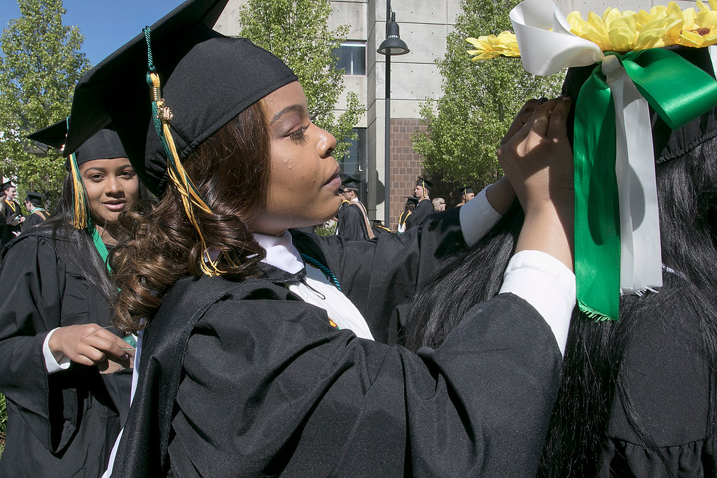 . The 123rd Commencement ceremony for Undergraduates was held at Fitchburg State University on Saturday, May 18, 2019. Jaynelle Williamson from Boston helps her classmate Joslyne Cox of Lowell with her mortar board as they get ready for the ceremony to start.  SENTINEL & ENTERPRISE/JOHN LOVE