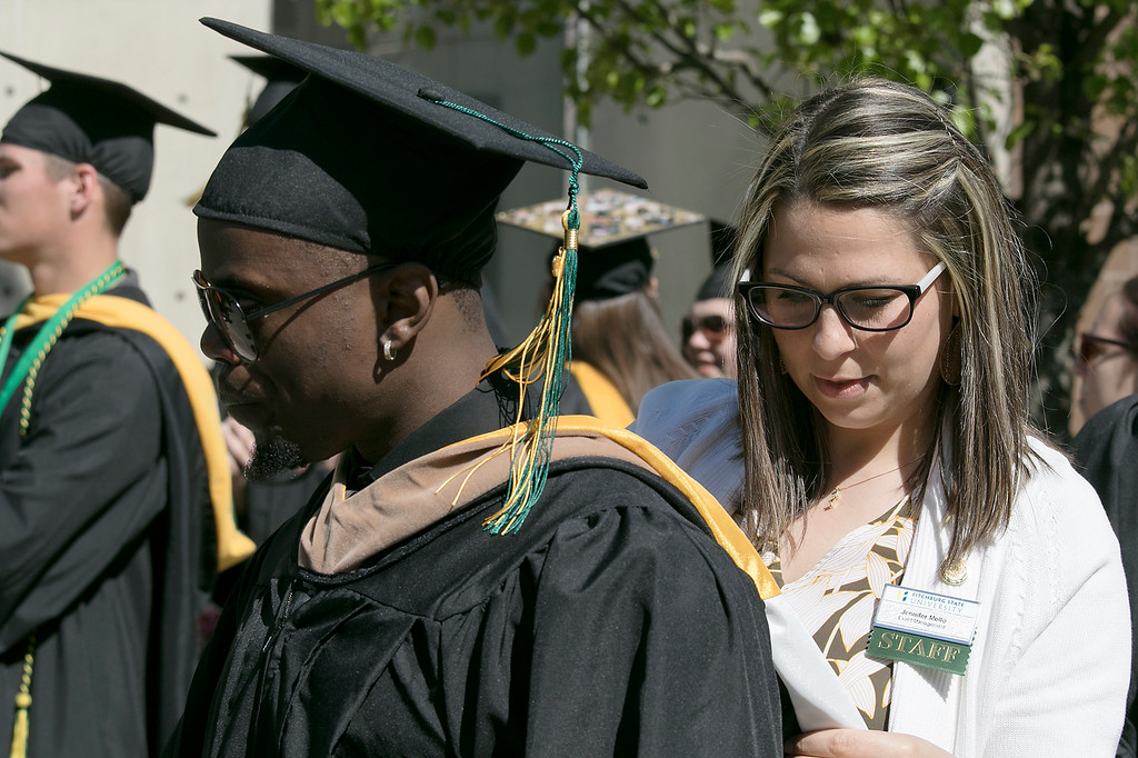 . The 123rd Commencement ceremony for Undergraduates was held at Fitchburg State University on Saturday, May 18, 2019. FSU Event Manager Jennifer Mello helps Christopher Tamukedde form Lowell with his rob and sash as they wait for the ceremony to start. SENTINEL & ENTERPRISE/JOHN LOVE