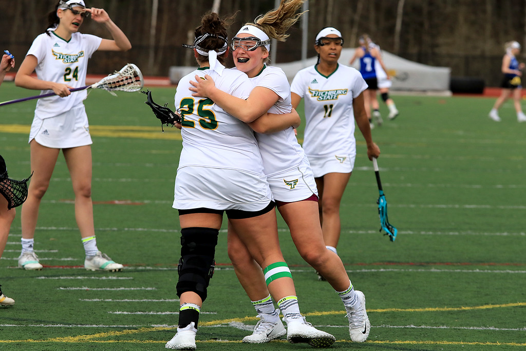 . Fitchburg State University women\'s lacrosse played Colby Sawyer on Tuesday afternoon at FSU\'s Elliot Field in Fitchburg. FSU\'s Tracy Long (25) celebrates her 100th career point during the game with teammate Julia Miele. Fitchburg State lost, 11-10. SENTINEL & ENTERPRISE/JOHN LOVE