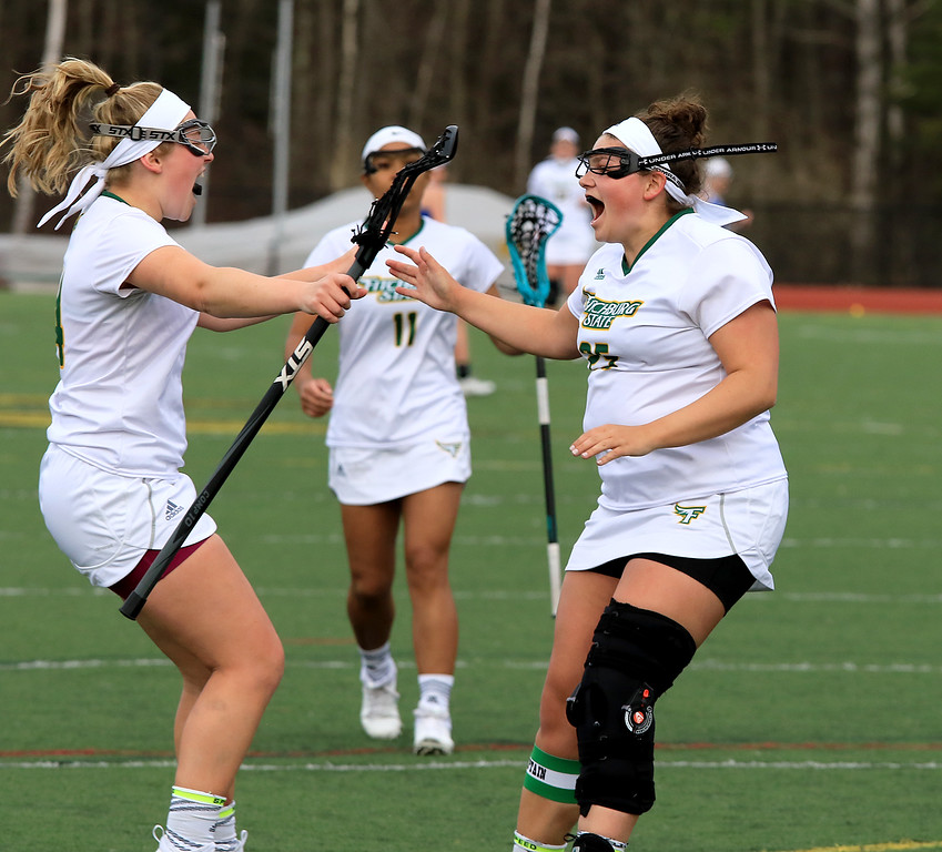 . Fitchburg State University women\'s lacrosse played Colby Sawyer on Tuesday afternoon at FSU\'s Elliot Field in Fitchburg. FSU\'s Tracy Long celebrates her 100th career point during the game with teammate Julia Miele. SENTINEL & ENTERPRISE/JOHN LOVE
