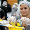 "The incoming freshmen class at Fitchburg State University helped package up tjhe stuff to make minestrone soup in the gym at the university's Recreation Center on Tuesday morning. This project is sponsored by the United Way of North Central MA. and the University and is part of the students orientation. All of the ingredients for the soups is brought by ""The Outreach Program."" The ingredients for the soup is pasta, pinto beans, soy beans, dehydrated vegetables and red sauce. Freshman Emma Garneau helps fill bags with the ingredients during the event. SENTINEL & ENTERPRISE/JOHN LOVE"