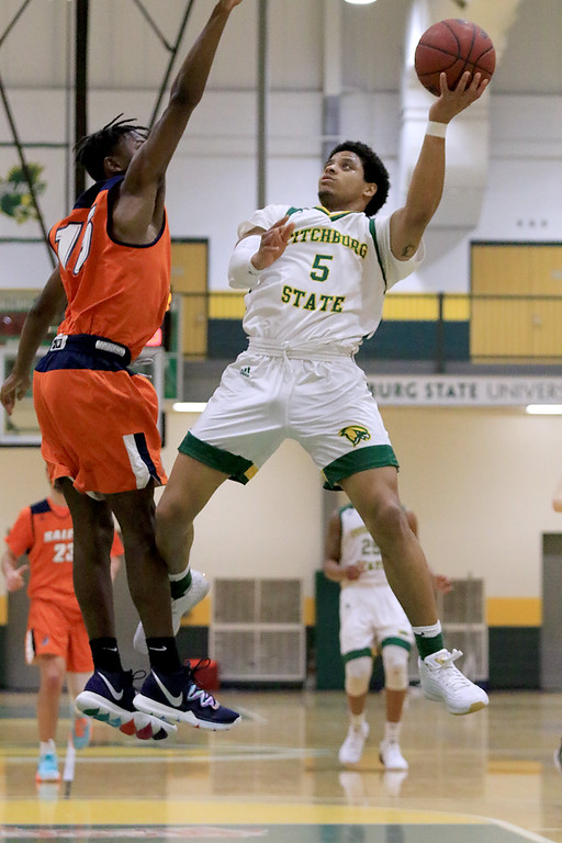 . Fitchburg State University men\'s basketball played Salem State University on Tuesdsay night, January 9, 2019 at FSU\'s Recreation Center. FSU\'s Jonathan Perez puts up a shot over SSU\'s Fern Berard during action in the first half of the game. SENTINEL & ENTERPRISE/JOHN LOVE