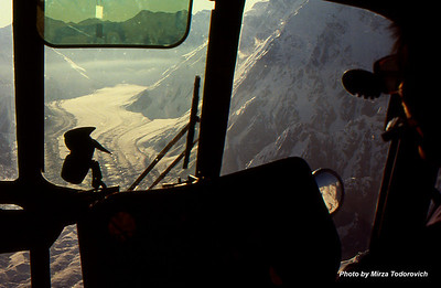"The largest glacier in the Tien Shan is Inylchek( Engilchek) Glacier, which is approximately 37 miles (60 km) long; it descends from the western slopes of the Khan Tängiri massif and branches into numerous tributaries. View from MI8 helicopter cabin.  - Najveci glecer na Tien Shan planinama je Inylchek (Engilchek) glecer, dugacak preko 60km (37 mls), nastaje u podnozju Khan Tengri vrha (Tengri Tag lanac vrhova) i prihvata veliki broj manjih glecera, ""pritoka"". Pogled iz kabine MI8 helikoptera."