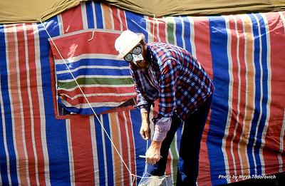 """Hamo is tying cords on the main tent. He is using custom sun protection for his nose. :)  - Hamo radi na zatezanju glavnog satora, koji ce bite mjesto druzenja, planiranja i kao """"trpezarija"""". Koristi specijalno napravljen stitnik protiv sunca. :)"""