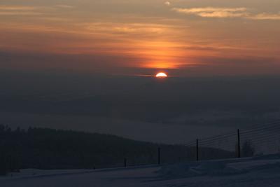 Solen går ned en vinterdag på Farbergshagen gård.