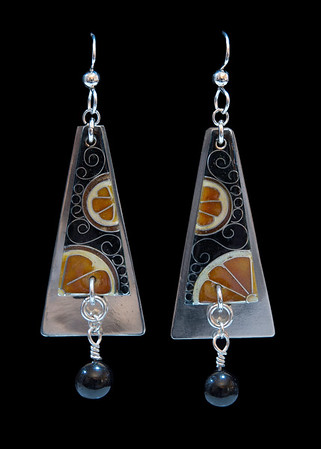 Cloisonné trapezoid shapes featuring juicy orange sections and fine silver scrolls. The cloisonné piece is affixed to an Argentium silver back and features a black tourmaline bead dangle. All findings are Argentium silver. Approximately 2 3/4 inches from top of ear wire to bottom of bead. 150.00