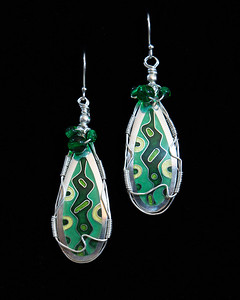 Fine Silver Champlevé and Cloisonné earrings in retro 50's pattern. Framed with Fine Silver wire wrap, garnished with green glass beads. Earrings are approximately 2 1/4 inches long by 3/4 inches wide at widest point. Drop from earwire is approximately 2 3/4 inches.  Sterling Silver ear wires. 120.00