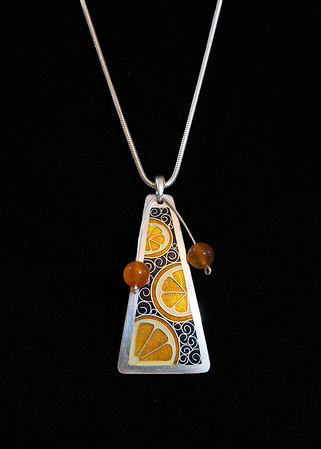 "Fine Silver Champlevé and Cloisonné orange slices. Complimented by carnelian bead ""mobile"" for some movement.  The pendant itself is 2 1/4 inches long by 1 1/4 inches wide and is supported on a 16 inch Sterling Silver snake chain. 275.00"