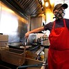BEN GARVER — THE BERKSHIRE EAGLE<br /> Miguel Gomez, owner of La Fogata in Pittsfield, cooks with a homemade mask and gloves.<br /> Friday, May 1, 2020.