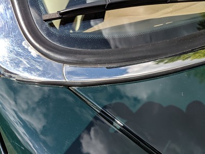 BEFORE - Note. small bubbles appearing from beneath the black rubber trim under the stainless-steel windscreen trim