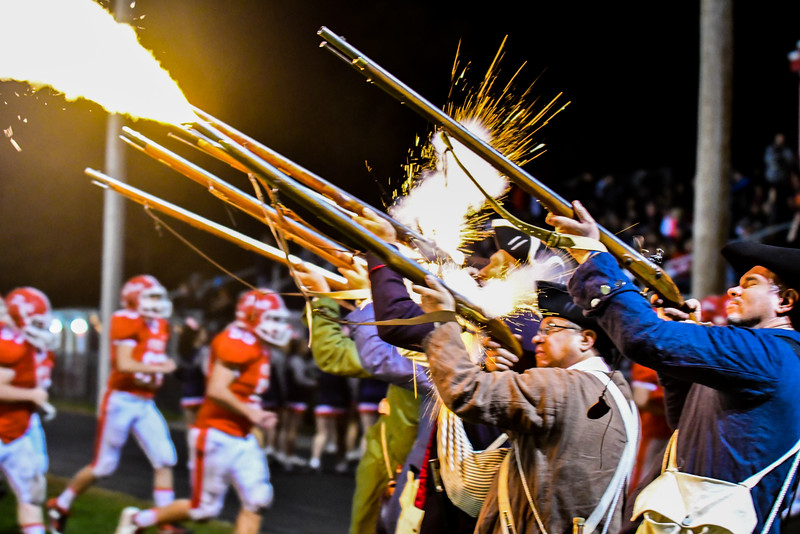 Members of the Middlesex 6th Regiment fire their muskets at the end of the first half of Friday night's North Middlesex Regional game. Nashoba Valley Voice/Ed Niser