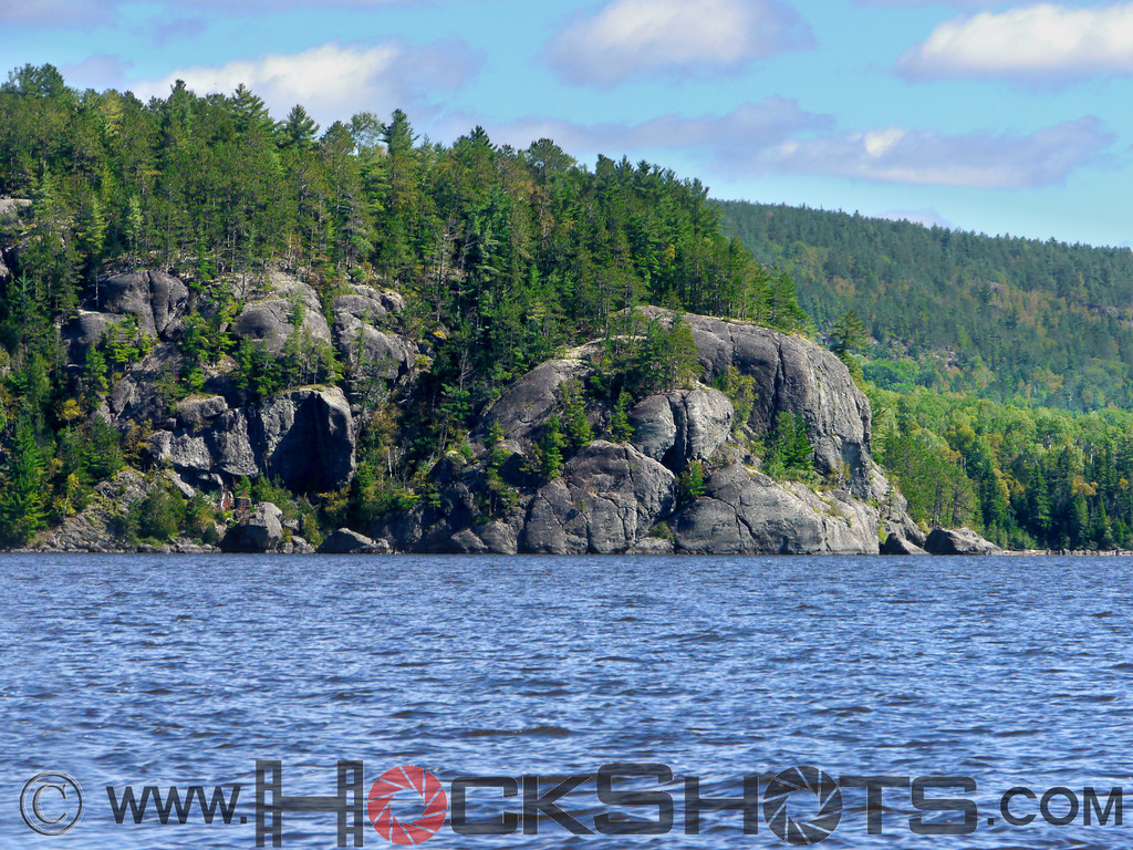 Here's a section of shoreline on the Quebec side of Lake Temiskaming. The rounded rock on the right could be the right-facing forehead of a large, bald, half submerged face, with the water line just above the lips.