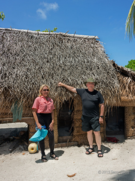 Couple in front of typical Bodaluna Island house with low doors, Laughlan Islands, PNG