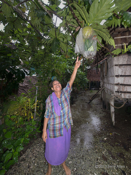 Villager showing off her papaya, Bonarua Is, Bumer Islands, PNG<br /> <br /> The papaya is wrapped in plastic to keep off the insects.