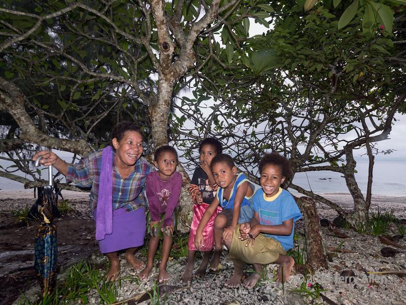 Vilage elder with children by the seashore, Bonarua Is, Bumer Islands, PNG