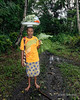 Woman carrying tray of food on her head, Fergusson Is, D'Entrecasteaux Islands, PNG