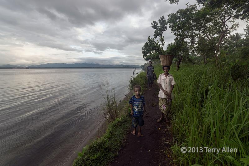 Family walking along a beach path, Fergusson Is, D'Entrecasteaux Islands, PNG