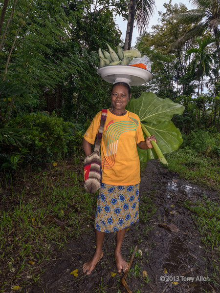 Woman with tray of vegetables on her head, Fergusson Is, D'Entrecasteaux Island, PNG