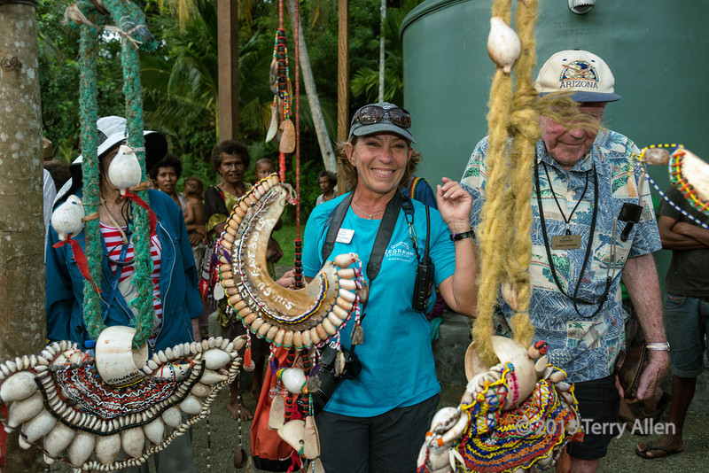 """So this is what all the fuss is about! (more photos from Dobu Island can be seen here <a href=""""http://goo.gl/kiJTu"""">http://goo.gl/kiJTu</a>)<br /> <br /> Shirley Campbell with kula necklace (center) and two bracelets (either end).  Shirley is an anthropologist who is a notable expert on the Kula Trade; she wrote the book """"The Art of Kula"""".  The valuable (kula) parts of the necklaces are the two round shell arm bands (which are male), and the red beads on the necklace (which are female).  The rest of the stuff is attached decorations.  Over time a man gains fame and prestige by transacting shells of high quality (= high rank).  The oldest, largest, highest rank Conus shells have unique names.  Only large shells can move up through the ranks to achieve fame and unique personal identities.  You can tell their age by their color.   New shells are white and the older ones gather a yellow, then red patina as they are handled. So the shell on the right of the photo is more valuable since it is larger and darker coloured.  The necklaces are made of red spondylus shell.  A high ranking shell string is very thin and very smooth from repeated handling.  Some high ranked name shells have been circulating continuously for 100 years or more, and serve as a medium for fostering relationships between people.  OK, enough about the kula stuff, already; Dobu has some cool witches that I'll tell you about in another post.<br /> <br /> I'm really chuffed that some of my work is profiled in the new issue of Jim Zukerman's Photo Insights Magazine. Jim is a world-renowned professional photographer, and I can certainly recommend his on-line magazine for all the wonderfully helpful tips that he gives to photographers each month. There is a link to all the previous issues near the back of this month's issue. <a href=""""http://issuu.com/jimzuckerman/docs/june__13"""">http://issuu.com/jimzuckerman/docs/june__13</a> edit"""