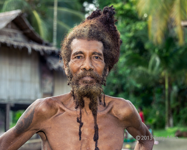 """Bewitched man, Dobu Island, D'Entrecasteaux Islands, PNG (see below for explanation of why he was bewitched, and to see a photo of Dobu Island and some Dobu warriors click here <a href=""""http://goo.gl/iuu5r"""">http://goo.gl/iuu5r</a>)<br /> <br /> Dobu Island is one of the D'Entrecasteaux Islands, which are a group of active volcanic islands north of Papua New Guinea. In the past, Dobu Island was known throughout Melanesia for its witchcraft, headhunting and cannibalism.  It was viewed with fear and awe; its people were envied for their power and influence, but also despised as barbarians. <br /> <br /> Dobu Island has always been a critical link in the kula trade that knits together the Melanesian Islands.  The Kula Ring is a fascinating tradition where participants travel hundreds of miles by canoe in order to exchange Kula valuables, which consist of red shell-disc necklaces that are traded with islands to the north (circling the ring in clockwise direction) and white shell armbands that are traded in the southern direction (circling counterclockwise). All Kula valuables are traded solely for the purposes of enhancing one's social status and prestige. You can read more about this fascinating tradition, first documented by the anthropologist Bronislow Malinowski, here <a href=""""http://en.wikipedia.org/wiki/Kula_ring"""">http://en.wikipedia.org/wiki/Kula_ring</a>.<br /> <br /> An important aspect of the Kula Ring is that the kula objects have to keep circulating.  Because of the prestige associated with the objects, however, there is a temptation to try to keep them.  This man was bewitched by a local sorcerer as a punishment because he broke the Kula Ring by keeping an important kula object (hence preventing it from circulating).  He certainly appeared to be off his rocker, and I was told that he was expected to die within a few months from the curse.  He was always on the move, muttering to himself, and hard to photograph, but I spoke a few words to him in his local lan"""