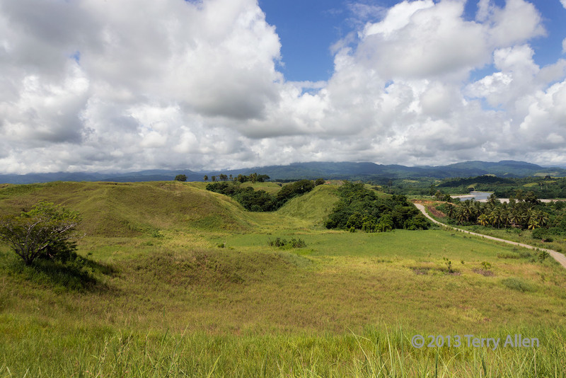 "Site of the decisive Battle of Edson's Ridge, with the strategic hills 123 and 80 and the Lunga River (mid far right), Guadalcanal Is, Solomon Islands<br /> <br /> Perhaps the most savage and bloody, yet largely forgotten, military campaigns in the Pacific War between the US and Japan, revolved around the island of Guadalcanal. For over six months forces of Japan and the United States were locked in a bitter struggle on land, sea and in the air.  <br /> <br /> The Americans were successful in capturing Lunga Point, which was the Japanese airfield.  They renamed it Henderson Field, and it was to be a vital link in the resupply chain for the Allied defense of New Guinea and Australia.  The Japanese mounted an attack to win back the airfield, whose perimeter was defended at the Lunga Ridge in the south of the airfield, which became known as Edson's Ridge after the US forces commander ""Red' Mike Edson.  Although the Americans were almost overrun by the Japanese, in the end the attack was defeated with heavy losses for the Japanese.  The battle took place between the 12-14 September 1942, with the Japanese attacking at night on two flanks.  The Japanese almost over-ran the Americans on the 2nd night as the Marines were not only  greatly outnumbered but were short of ammunition and supplies, and had no possibility of resupply.  <br /> <br /> In the end the Battle of Edson's Ridge was one of the most decisive victories of the war in the Pacific since it had a strategic impact on the Japanese operations in other parts of the Pacific.  The Japanese realized that, in order to send enough troops and supplies to defeat the Allies on Guadacanal, they could no longer support the offensive in Papua New Guinea to capture Port Morseby, which was the doorway to an attack on Australia. The defeat at Edson's Ridge contributed not only to Japan's defeat in the Guadalcanal campaign, but also to Japan's ultimate defeat throughout the South Pacific.  Historian Richard B Frank has written ""The Japanese never came closer to victory on the island itself (Guadacanal) than in September 1942, on a ridge thrusting up from the jungle just south of the critical airfield, best known ever after as Bloody Ridge.<br /> <br /> A couple of photos of Honiara locals can be seen here: <a href=""http://goo.gl/yq9KRK"">http://goo.gl/yq9KRK</a><br /> <br /> 04/12/13  <a href=""http://www.allenfotowild.com"">http://www.allenfotowild.com</a>"