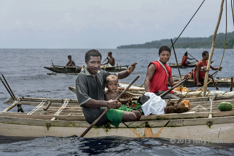 Village men and a baby on outrigger canoes, Kitava Island, Trobriand Islands, PNG