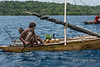 Islander in outrigger canoe with coconuts and pineapple, Kitava Island, Trobriand Islands, PNG