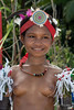 "Portrait of a girl-6, Kitava Island, Trobriand Islands, PNG<br /> <br /> The Trobrianders practice many magic spells, and the spells for beauty are  are chanted into coconut oil, and then a person rubs it onto their skin, or into flowers and herbs that decorate their armbands and hair, as you can see here.  (This apparently works even for 'ugly' people).<br /> <br /> In the early 1900s, the anthropologist Bronislaw Malinowski lived for several years with the Trobriand Islands and he wrote a series of groundbreaking books that still make entertaining reading today. A short summary of Malinowski's observations can be read here: <a href=""http://www.aaronsw.com/weblog/savagesex"">http://www.aaronsw.com/weblog/savagesex</a>.<br /> <br /> In Malinowski book 'The Sexual Life of Savages' he describes the fascinating sexual customs of the islanders where girls as young as 6-8 start freely having sex, and boys as young at 10-12 years old.  As in this photo, the girls went topless, although this is now starting to change due to the influence of the missionaries.<br /> <br /> Malinowski describes how, despite having sex from an early age, the girls rarely get pregnant, and the people don't believe that sex is the cause of pregnancy.  They believe that when people die their spirit takes a canoe to the island of Tuma, and when their spirit get old it shrugs off its skin and turns into an embryo, which a spirit takes back to the island of the living and inserts into a woman and makes her pregnant.  Apparently this belief in the lack of  connection between sex and pregnancy can still be found today. Since they don't believe that sex causes pregnancy, there is no concept of fatherhood and the society is matrilineal since you can always be sure who your mother is, even if there is no 'father'.  However the mother's husband shows great care and concern for the children.<br />   <br /> Malinowski's work influenced the young Margaret Mead, whose famous book ""Coming of Age in Samoa"" influenced the sexual revolution of the 1960s.  Her description of matrilineal societies such as the Trobriand Islands ('Sex and Temperament in Three Primitive Societies') was the cornerstone of the feminist movement.<br /> <br /> Some other portraits of Trobriand girls can be seen here: <a href=""http://goo.gl/92JRv"">http://goo.gl/92JRv</a><br /> <br /> 125 mm, 1/125 sec, f11, ISO 280, flash fill"