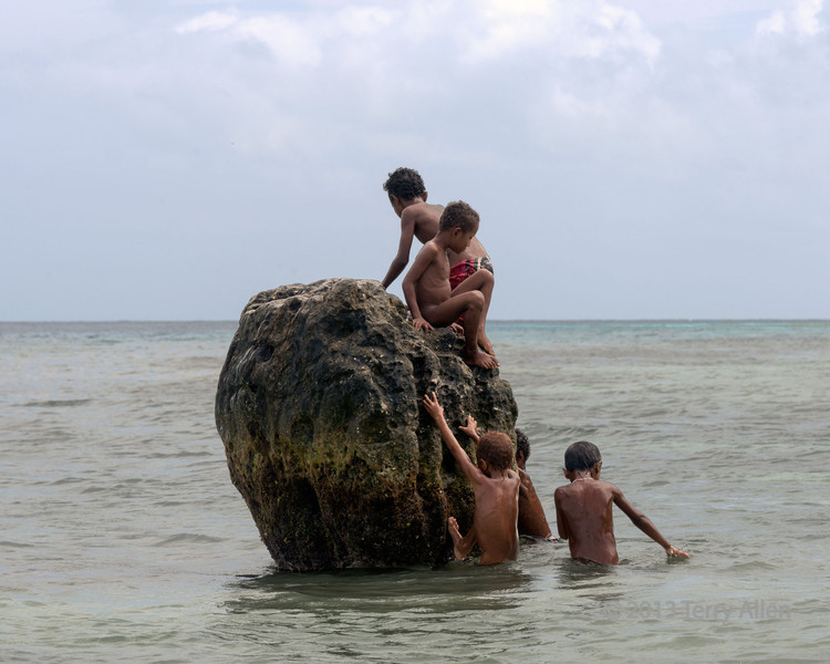 Boys playing on dead coral, Kitava Island, Trobriand Islands, PNG
