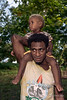 Father carrying son on his shoulders, Santa Ana Island, Solomon Islands